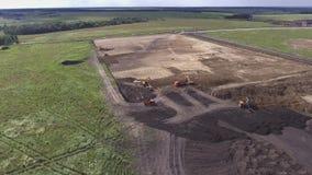 Luchtvlucht over aarde bewegende machines en bouwwerf Vlucht over het gebied waar het bouwmateriaal stock videobeelden