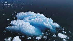 Luchtvlucht over ijsberg in de oceaan van Antarctica stock footage
