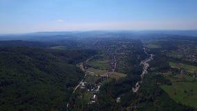 Luchtvlucht over Polovragi-commune en groene heuvels, Roemenië stock video