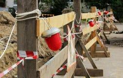 Luci d'avvertimento rosse che che accludono la fossa, dove la riparazione delle tubature dell'acqua Fotografia Stock Libera da Diritti