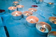 Luci del tè della candela sull'altare della chiesa Fotografia Stock