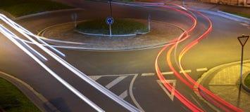 Luci dell'automobile alla rotonda alla notte immagini stock libere da diritti
