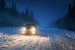 Luci dell'automobile nella foresta di inverno Fotografie Stock Libere da Diritti