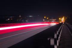 Luci dell'automobile sulla strada principale con una notte scura immagine stock