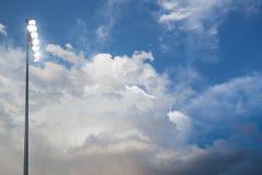 Luci dello stadio di football americano con il cielo nuvoloso nei precedenti fotografie stock libere da diritti