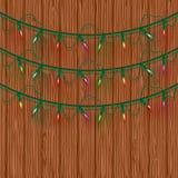 Luci di Natale multicolori d'ardore tre linee su fondo di legno Modello per progettazione delle cartoline d'auguri di festa di na royalty illustrazione gratis