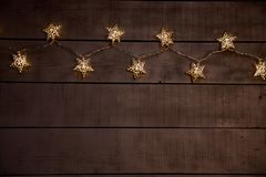 Luci di Natale stellate su un fondo di legno grigio fotografia stock