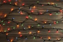 Luci di Natale su fondo di legno scuro Fotografie Stock