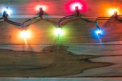 Luci di Natale su legno per fondo immagine stock