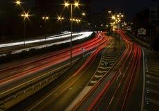 Luci lunghe dell'automobile della strada principale di esposizione alla notte Fotografia Stock