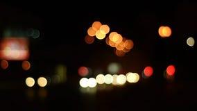 Luci notturne variopinte e passaggio dell'automobile di abbagliamento di un fondo vago stock footage