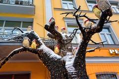 Luci su un albero sotto forma di gufo in cappelli di Santa Decorazione di costruzione moderna e gialla per il Natale fotografia stock libera da diritti