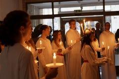 Lucia-Parade mit Gesangmädchen und Jungen im weißen Kleid-holdin Lizenzfreie Stockfotos