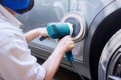 Lucidatura del lavoratore un'automobile con il lucidatore automatico fotografia stock libera da diritti