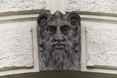 Lucifer雕塑面对与垫铁 邪魔邪恶的mascarone建筑学元素大厦的门面背景 浅 免版税库存照片