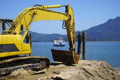 Lucinda beach erosion. Excavator on the beach moving sand and repair erosion after tide damage stock images