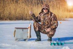 Lucio de la captura del pescador en la pesca del invierno Foto de archivo libre de regalías