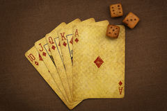 Luck of the gambler. Wonderful poker combination and not-so-bad dice alignment shooted with retro-stuled playing cards and wooden dices stock photos