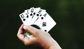 Luck is in my Hand. Closeup shot of a human hand holding a glass ball in their cupped hand with a royal flush poker hand in spades fanned out in the hand behind Royalty Free Stock Photos