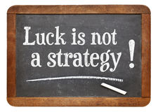 Luck is not a strategy. Advice on a vintage slate blackboard royalty free stock photography