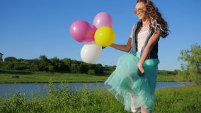 Lucky adolescent girl in sunglasses with balloons in hands walking on river bank on green grass. Lucky adolescent girl in sunglasses with balloons in hands stock video footage