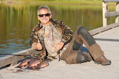 Lucky Angler with his Catch. A lucky fisherman poses with his catch of three Brook Trout on the fishing dock stock photo