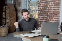 Lucky bearded hipster guy rejoices at his victory, looking in net-book stock image