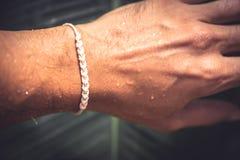 Lucky bracelet on wet tanned hand. Lucky bracelet on wet tanned men`s hand Royalty Free Stock Photo