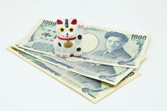 Lucky cat on Japanese Yen banknotes Stock Photos