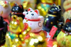 Lucky cat is symbol good luck. Cat attracts good luck, the figure waves a hand, a small statuette on the Hong Kong market stock image