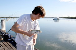 Lucky Catch. Young man fishing and has caught a fish Stock Photography