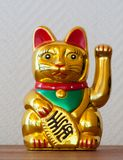 Calico Cat. A lucky charm and a golden, red, green toy stock image
