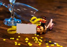 A lucky charm on New Year`s Eve. A chimney sweep on a pig with confetti, paper and champagne glasses royalty free stock image