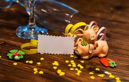 A lucky charm on New Year`s Eve. Lucky pigs with confetti, paper and champagne glasses royalty free stock images