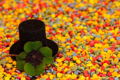 Lucky clover and a cylinder on colorful confetti Stock Photos