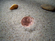 Lucky coin. Be lucky and find a 1 cent coin in the sand of a beach royalty free stock photography