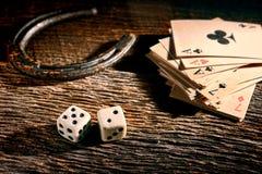 Lucky Craps Dice- und Poker-Karten durch altes Hufeisen Stockfotografie