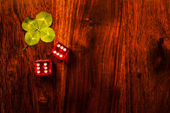 Lucky dice gamling. Two red dices with a luckycharm four-leaf clover Royalty Free Stock Photos