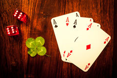 Lucky dice gamling. Two red dices with a luckycharm four-leaf clover Royalty Free Stock Photography