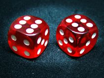 Lucky dice. Two six sided red dice with red dots and rounded edges. Made of plastic, look like candy, translucent, on rough black background Stock Photography
