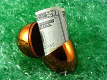 Lucky dollar. A bright shiny bronze egg broken in half to reveal American dollar bills Stock Image