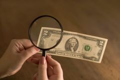 Lucky dollar in hand through a magnifying glass royalty free stock photography