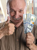 Lucky elderly man with dollar bills Stock Photos