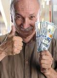 Lucky elderly man with dollar bills Stock Photos