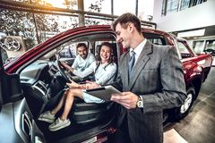 Lucky family sitting in new automobile in auto salon stock image