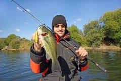 Man holding bass. Fishing scene, catch of fish stock photo