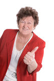 Lucky and funny old woman wearing red jacket - thumbs up. Royalty Free Stock Photography