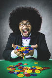 Lucky gambler holds gambling chips. Portrait of lucky gambler with Afro hair, winning a gambling and holding many chip on his hands with happy expression stock photography