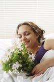 Lucky girl enjoying the fragrance of flowers Stock Image