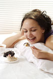 Lucky girl lies in bed and eating cake Stock Image